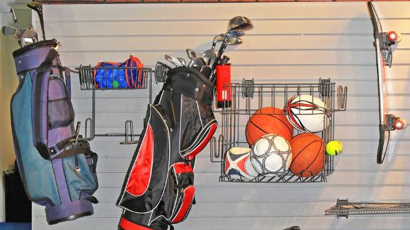 Sports equipment organized and hanging on wall of garage.