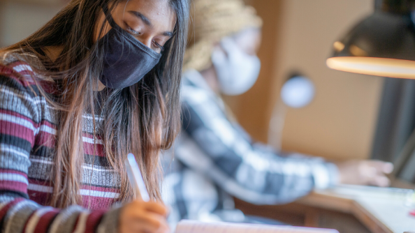 Female college student wearing face mask writing in notebook.