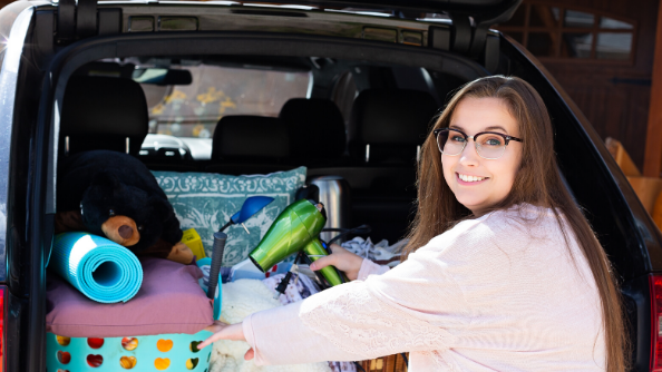 College age woman smiling while putting dorm room items in her car trunk.