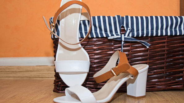 A pair of shoes sit next to a wicker basket.