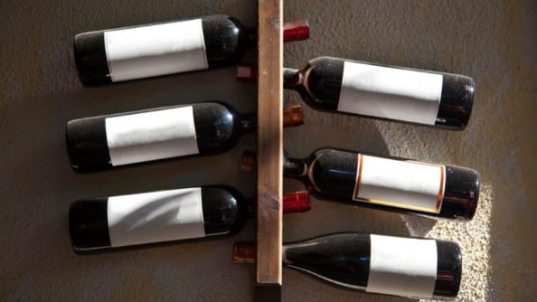 A wall mounted wine rack holding six bottles.