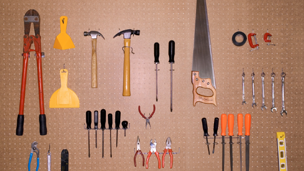 Various tools hanging on a pegboard.