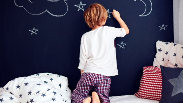 A child draws on a chalkboard wall next to their bed.