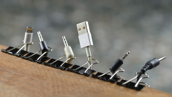 Six binder clips attached to a desk, holding various cables and wires.