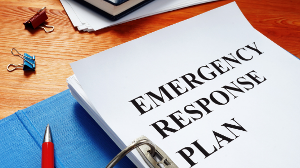 """A folder with a title page """"EMERGENCY RESPONSE PLAN"""" opened on a desk."""