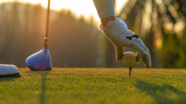 A golfer sets their golf ball on top of a tee, preparing to line up a shot.